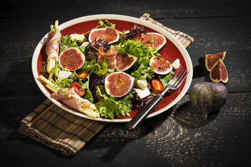 Mixed salad with figs, tomatoes, sheep cheese, grissini with ham on plate - MAEF12733