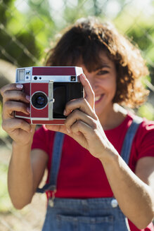 Smiling woman taking picture with instant camera - KKAF01560