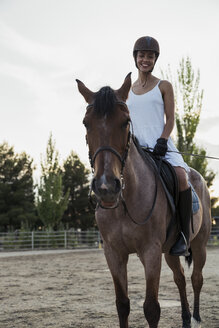 Smiling woman siiting on horse - KKAF01578