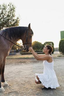 Smiling woman stroking horse - KKAF01587
