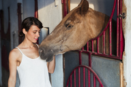 Portrait of woman stroking horse in stable - KKAF01593