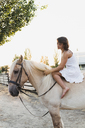Barefoot woman sitting bareback on horse - KKAF01602