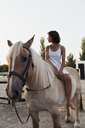 Barefoot woman sitting bareback on horse - KKAF01605