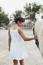 Back view of woman in white dress leading horse - KKAF01617