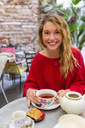 Portrait of smiling young woman with tea cup at pavement cafe - MGIF00238