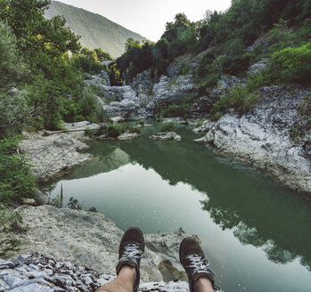 Italy, Marche, Fossombrone, Marmitte dei Giganti canyon, Metauro river, hiker sitting on riverside, shoes - LOMF00745