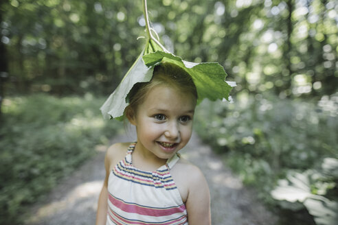 Portrait of smiling little girl with leaf on her head - KMKF00460