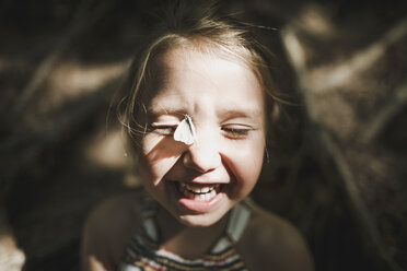 Portrait of laughing little girl with butterfly on her face - KMKF00463