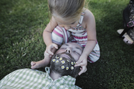 Little girl decorating father's beard with daisies on meadow in the garden - KMKF00466