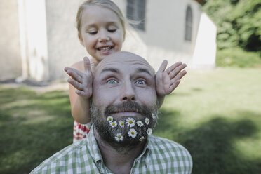 Portrait of mature man with daisies in his beard playing with little daughter in the garden - KMKF00469