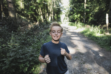 Portrait of smiling boy jogging in the woods - KMKF00472