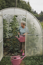 Senior woman with watering can in greenhouse - KMKF00475