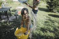 Brother and sister playing with water in garden - KMKF00505