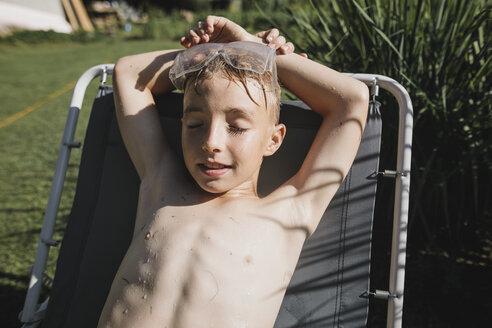 Wet boy wearing safety goggles lying on sun lounger in garden - KMKF00508