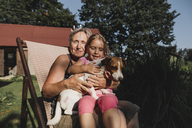 Smiling grandmother with granddaughter and dog on deckchair in garden - KMKF00511