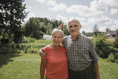 Portrait of happy senior couple standing in the garden - KMKF00516