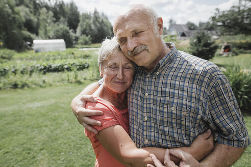 Portrait of happy senior couple embracing each other in the garden - KMKF00519
