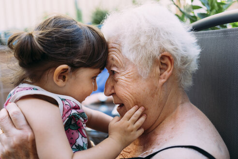Grandmother face to face with her  granddaughter on terrace - GEMF02374
