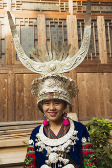 China, Guizhou, portrait of a young Miao woman wearing traditional dress and headdress - KKAF01629