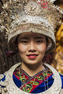 China, Guizhou, portrait of a young Miao woman wearing traditional dress and headdress - KKAF01632