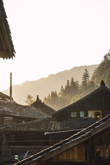 China, Guizhou, houses of a Miao settlement in backlight - KKAF01638