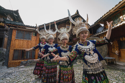 China, Guizhou, Miao women wearing traditional dresses and headdresses posing on village square - KKAF01644