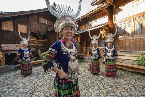 China, Guizhou, happy Miao women wearing traditional dresses and headdresses standing on village square - KKAF01647