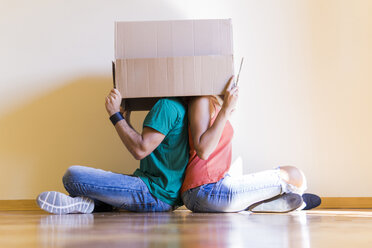Couple with heads in cardboard box sitting back to back on the floor at new home - FBAF00015