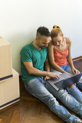 Couple sitting side by side on the floor of new home looking together at laptop - FBAF00018