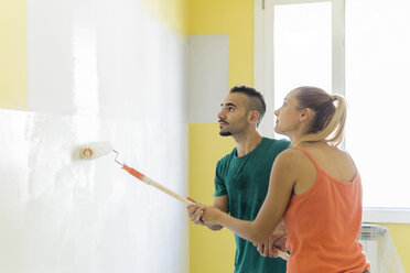 Couple painting wall together at new home - FBAF00033