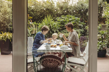 Two happy mothers at breakfast table outdoors with their child - MFF04417