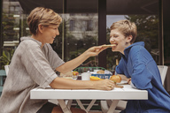 Two happy women at the breakfast table on their terrace - MFF04420