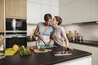 Happy lesbian couple in kitchen cooking together - MFF04423