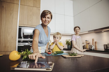 Happy lesbian couple and their child in kitchen - MFF04426