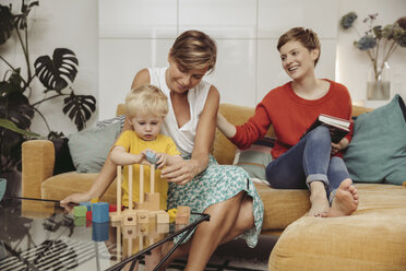 Two mothers learning and playing with their child at home - MFF04429