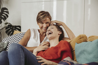 Happy lesbian couple laughing and cuddling on couch - MFF04438