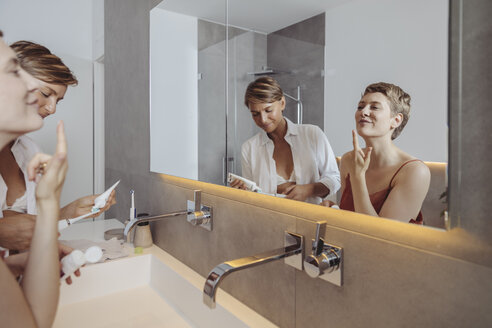 Lesbian couple getting ready for their day in the bathroom - MFF04444