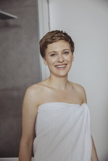 Portrait of happy women wrapped in towel standing in bathroom - MFF04450