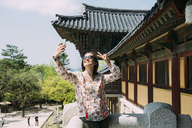 South Korea, Gyeongju, happy woman taking a selfie with cell phone in Bulguksa Temple - GEMF02396