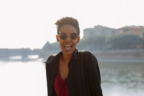 Italy, Verona, portrait of laughing young woman wearing sunglasses - GIOF04263