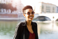 Italy, Verona, portrait of smiling young woman in front of Adige River - GIOF04266