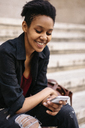 Portrait of smiling young woman sitting on stairs looking at cell phone - GIOF04269