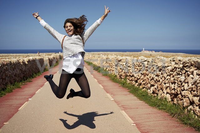Cheerful young woman jumping in air with rising hands, outdoors - IGGF00538