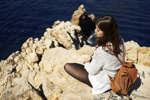 Young brunette woman sitting on coast, looking at view - IGGF00544