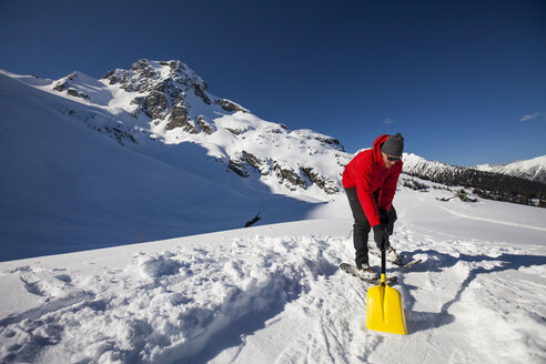 A climber shovels snow in order to make a flat spot to pitch his tent while camping below Joffre Peak. - AURF03611
