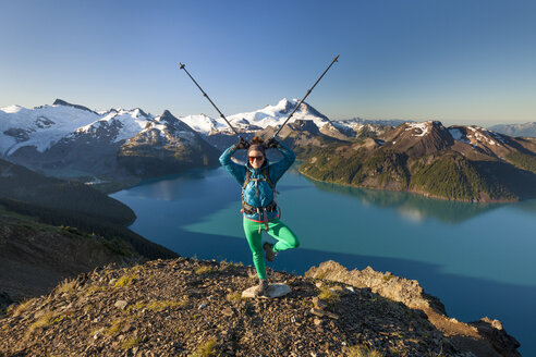 A backpacker makes a funny pose on the summit of Panorama Ridge in Garibaldi Provincial Park, British Columbia, Canada. - AURF03623