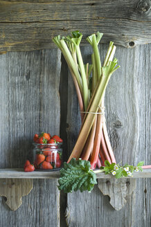 Bunch of rhubarb stalks and strawberries in a glass on rack - ASF06231