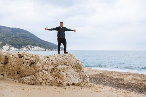 Italy, Vieste, relaxed man with arms outstretched standing on a rock on Vignanotica Beach - FLMF00006