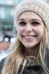 Portrait of smiling blond young woman wearing wool cap in winter - IGGF00548