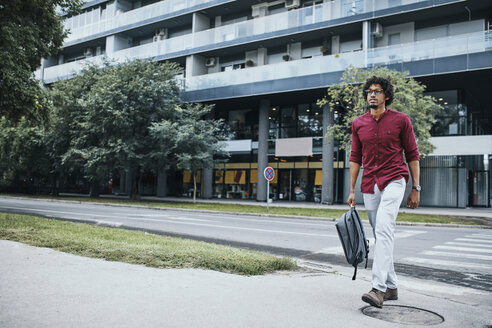 Young man going to work, crossing road - ZEDF01512